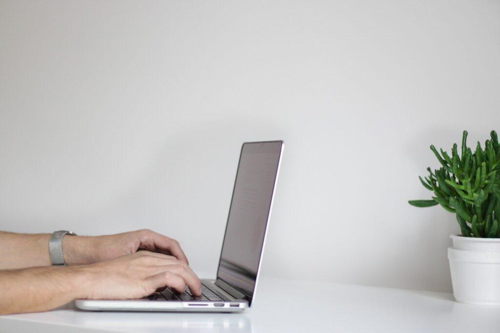 Zwei Hände schreiben auf einer Laptoptastatur
