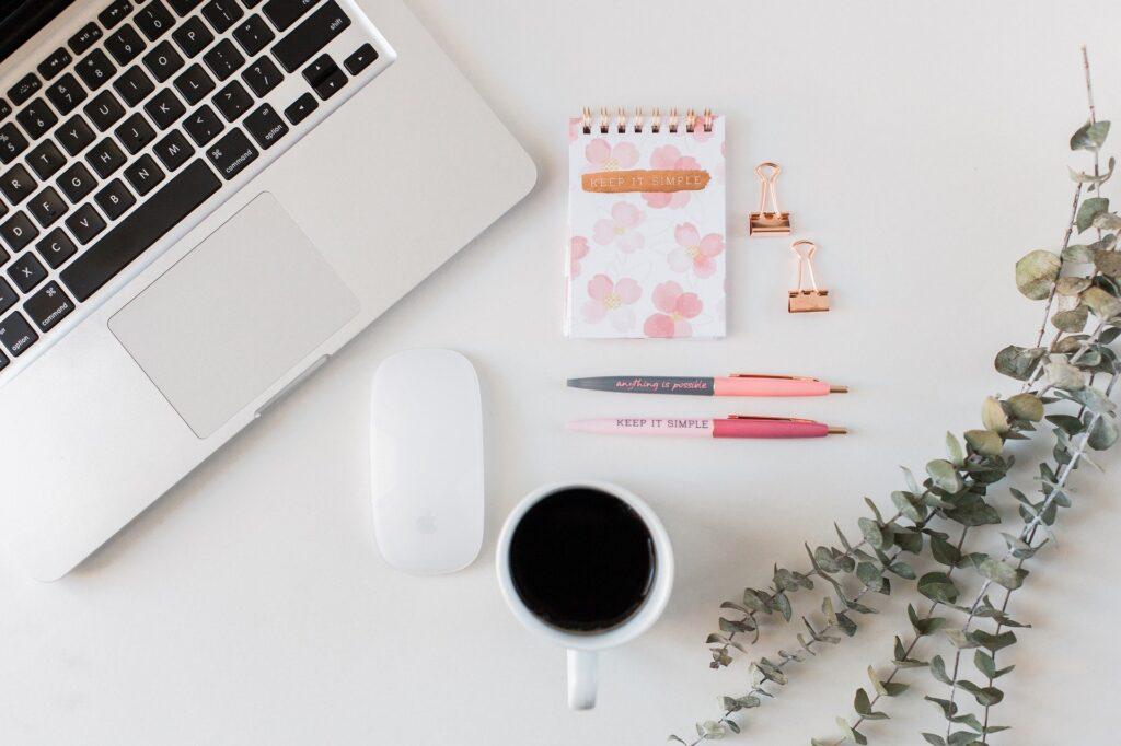 Schreibtischoberfläche mit Laptop, Stift und Notizblock