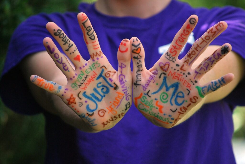 """Mit bunten Stiften beschriebene Hände. Hauptaussage """"Juste Me"""""""