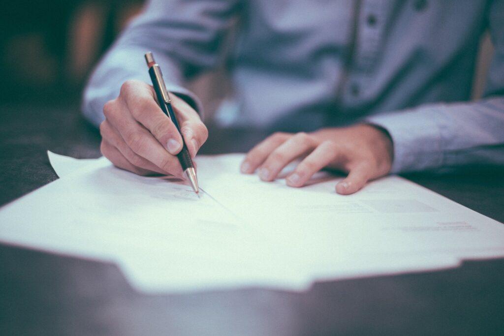Männderhände unterzeichnen Papierunterlagen