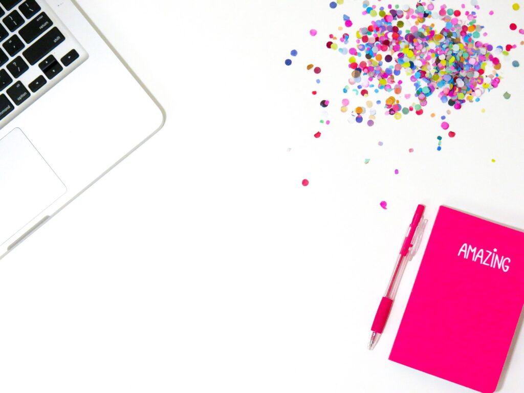 Laptop, buntes Konfetti und ein Notizbuch mit der Aufschrift Amazing