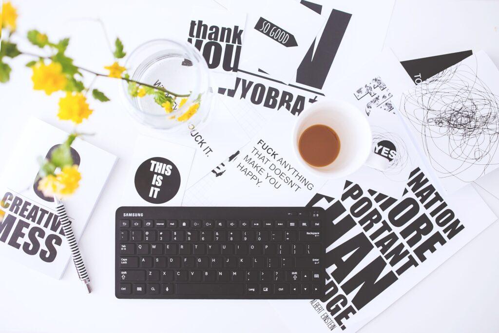 Viele Zettel mit kreativen Sprüche liegen verstreut auf einem Tisch. Dabei eine Tastatur, eine Tasse Kaffee und gelbe Blumen.