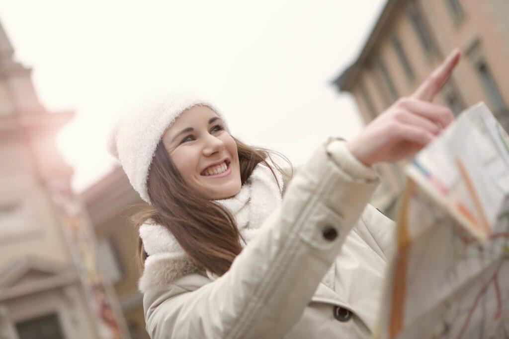 Mädchen hält eine Straßenkarte in der Hand und zeigt mit dem Finger in eine Richtung.