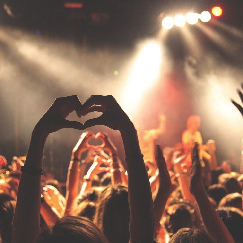 Menschengruppe bei einem Konzert. Eine Frau formt mit den Händen ein Herz.