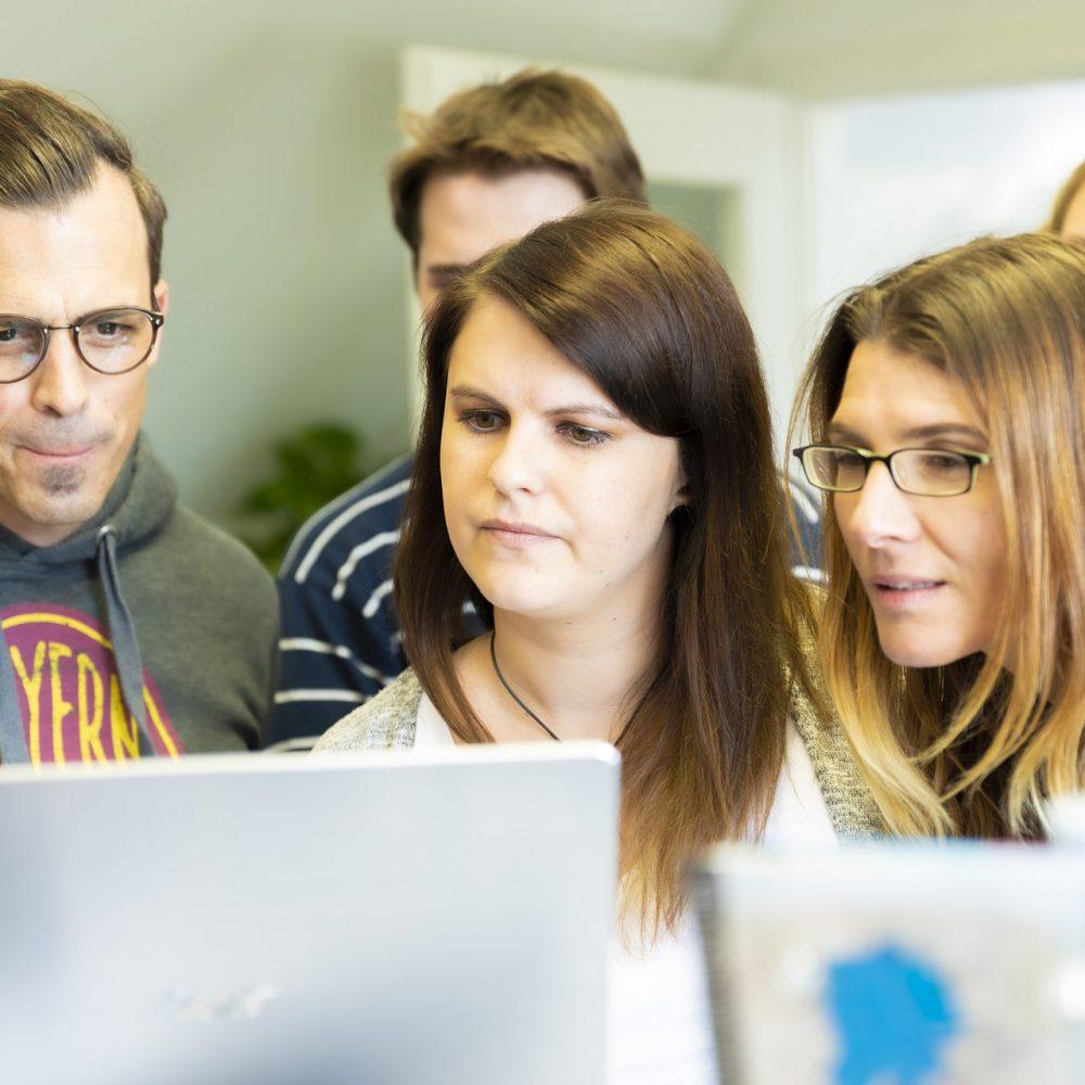 Gruppe junger Menschen schaut auf einen Laptop.